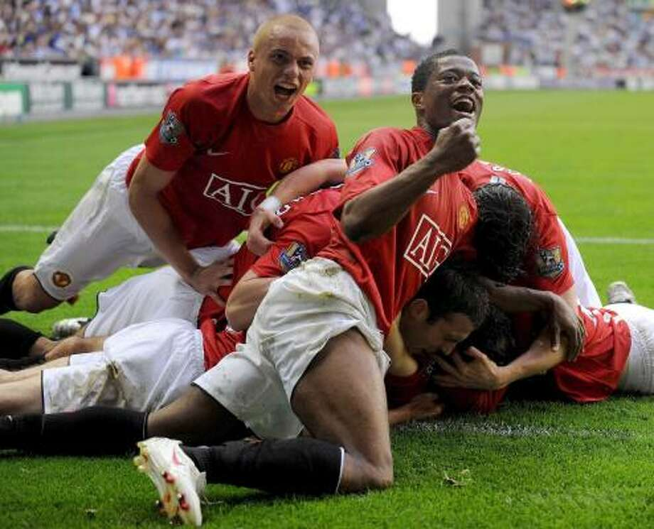 Manchester United players enjoy an insurance goal by Ryan Griggs in the 80th minute of a 2-0 win over Wigan. Photo: DAVE THOMPSON, ASSOCIATED PRESS