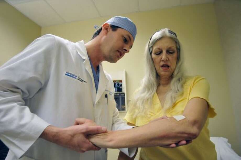 Dr. Craig Fischer examines patient Wanda Prouty's arm Aug. 7. Prouty has chronic pancreatitis. Photo: STEVE UECKERT, CHRONICLE
