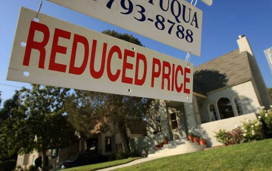 A real estate agent's sign in Pasadena, Calif. advertises that the price of a house has been reduced. Photo: DAVID McNEW, GETTY IMAGES
