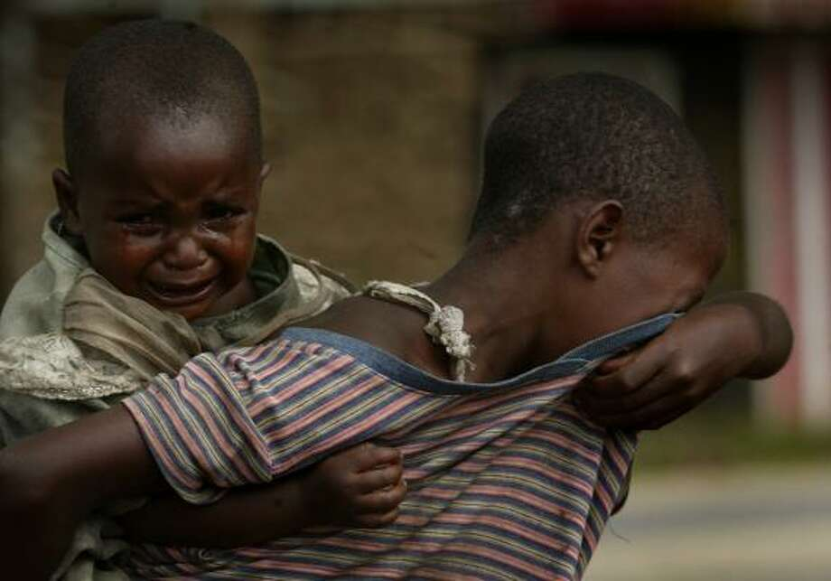 Two children cry as they look for their parents in Kiwanja, Congo, after the fighting there ended. Photo: JEROME DELAY, ASSOCIATED PRESS