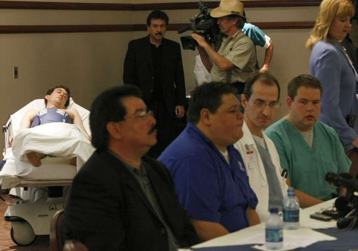 As injured singer Emilio Navaira's brother, Raul, discusses his brother's condition, research assistant Robert Funk, background, shows how the cooling therapy is applied.