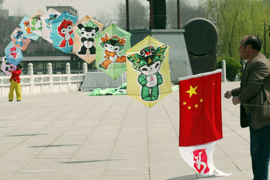 Chinese kite-flying enthusiasts prepare to launch a string of kites with the 2008 Beijing Olympics mascots in northern China's Shaanxi province on Saturday. Opponents of the nation's crackdown in Tibet say President Bush should skip the Games' opening ceremony to send a strong message to Beijing. Photo: STR, STR/AFP/Getty Images