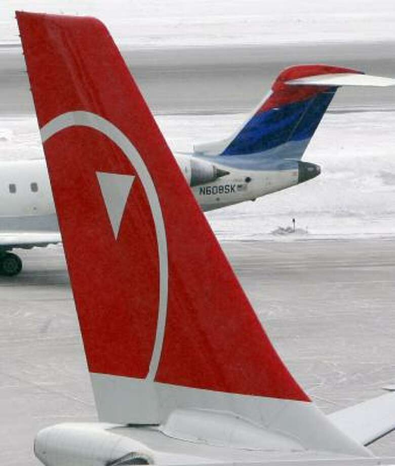 A Delta Connection plane taxis near a parked Northwest Airlines jet on Tuesday at Minneapolis-St. Paul International Airport. Sources say pilots unions at Delta and Northwest disagree on blending their seniority lists. Photo: JIM MONE, ASSOCIATED PRESS