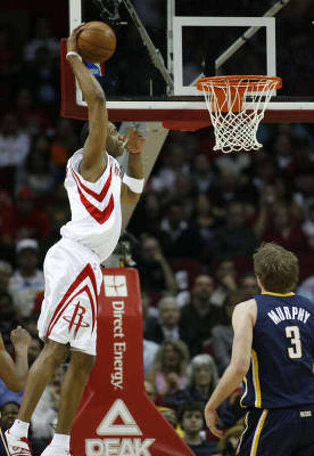 Tracy McGrady dunks over Pacers forward Troy Murphy during the Rockets' 16th straight win. Photo: Kevin Fujii, Chronicle