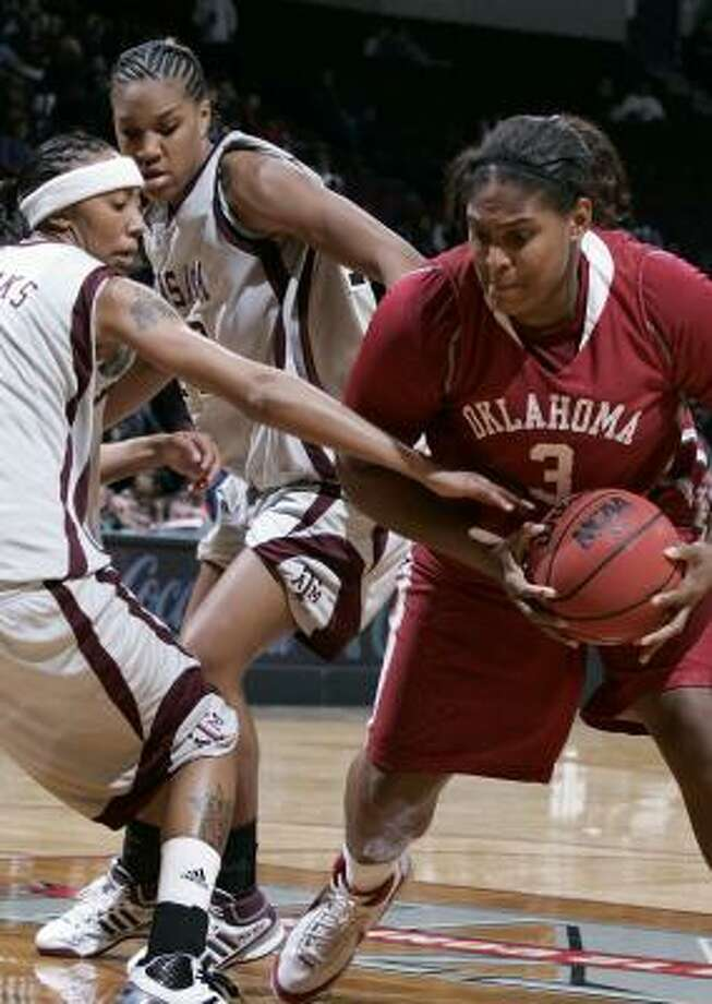 Oklahoma's Courtney Paris has her path blocked by Texas A&M's Takia Starks, left, and La Toya Micheaux. Photo: PAUL ZOELLER, AP