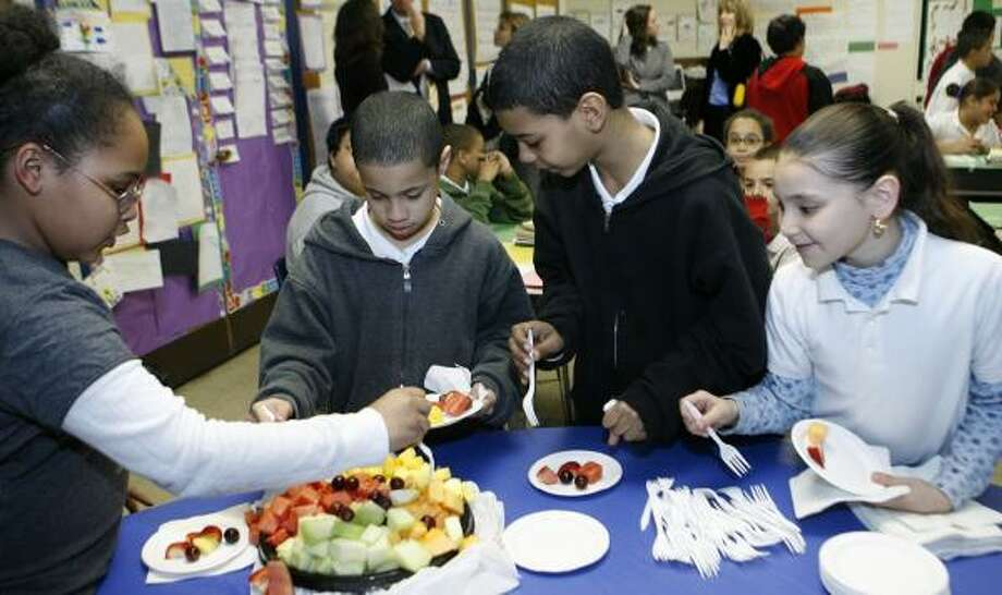 Fourth-graders in Philadelphia snack on fruit during a nutrition education activity. Some elementary schools there provided healthier choices for children during a two-year experiment. Photo: JOSEPH V. LABOLITO, TEMPLE UNIVERSITY/AP