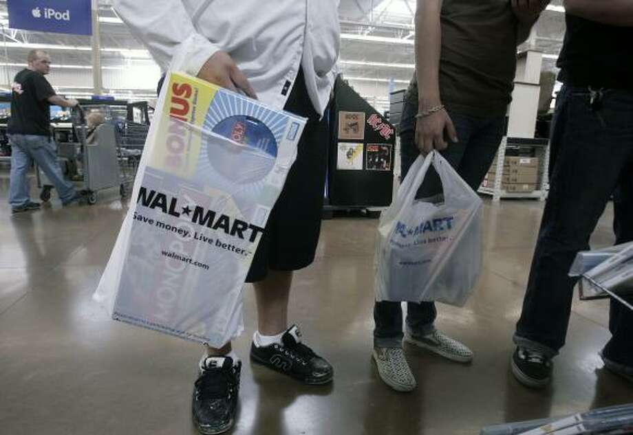 Shoppers browse in a Wal-Mart, in Rosemead, Calif., last week. As retailers report their September sales figures, it's clear that shoppers stuck to buying the essentials and looked for bargains. Even Wal-Mart reported that sales of discretionary items were weak. Photo: RIC FRANCIS, ASSOCIATED PRESS