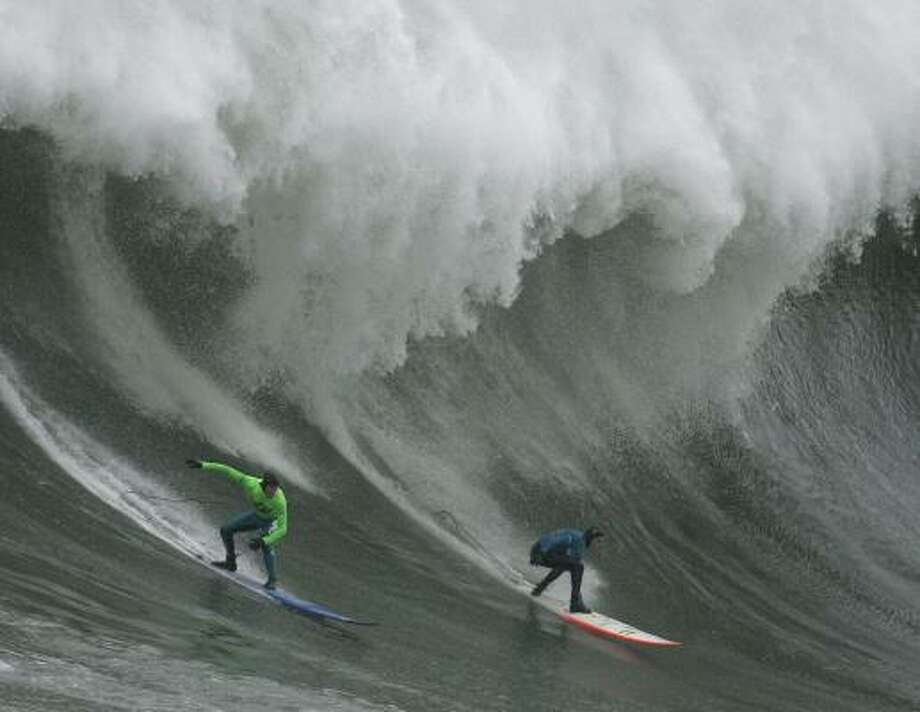 Contest winner Greg Long, left, and third-place finisher Jamie Sterling surf a giant wave Saturday. Photo: BEN MARGOT, ASSOCIATED PRESS