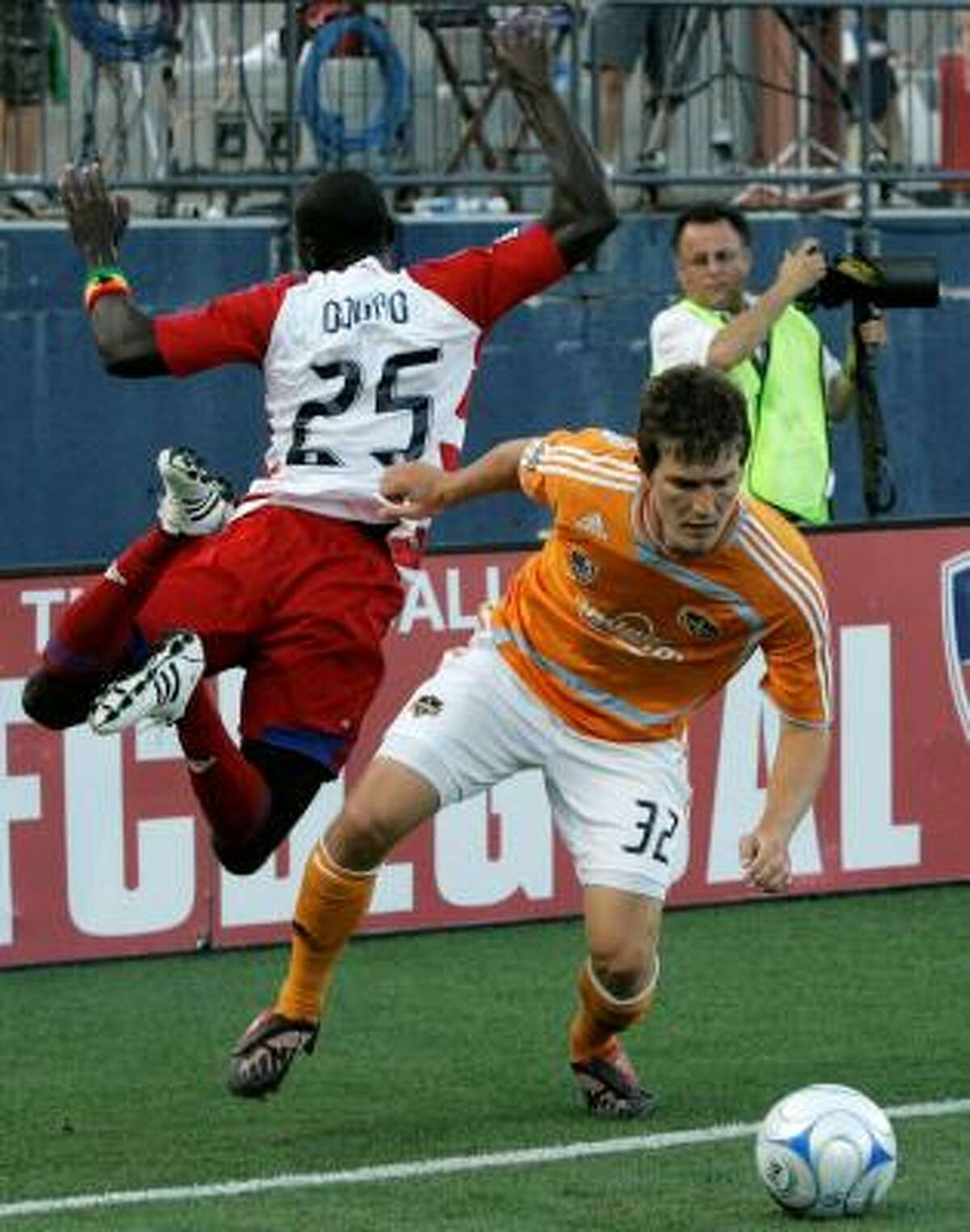 FC Dallas forward Dominic Oduro, left, is knocked out of bounds by Dynamo defender Bobby Boswell as they compete for a loose ball in the first half.