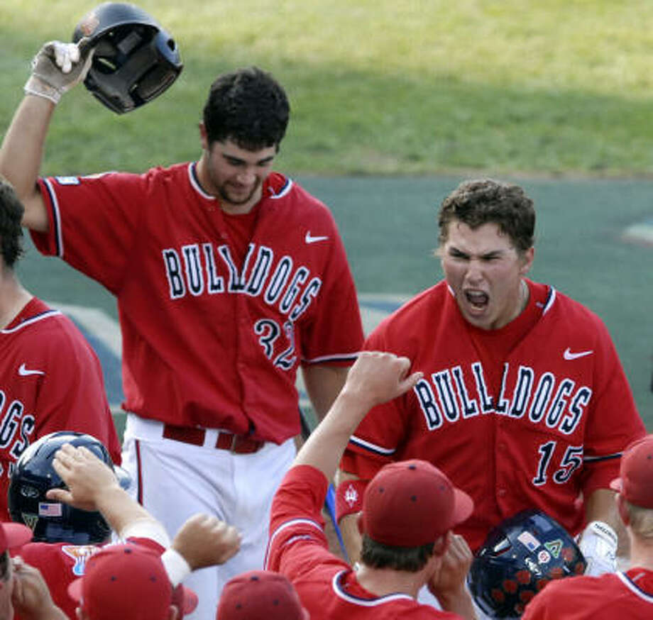 Fresno State's Steve Detwiler (15) celebrates with teammates after hitting a two-run homer in the second inning to give the Bulldogs an early 2-0 lead. Photo: Dave Weaver, AP