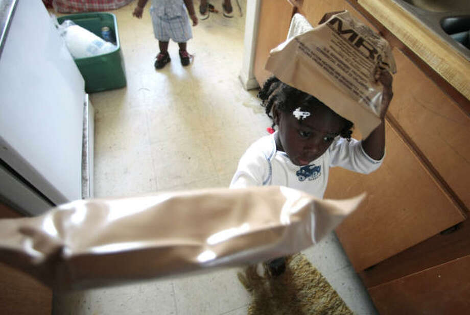 Jahnae' Nealy, 3, helps her grandmother tote MREs into their Third Ward apartment. The meals come with a heating element and don't require power to warm them. Photo: Billy Smith II, AP