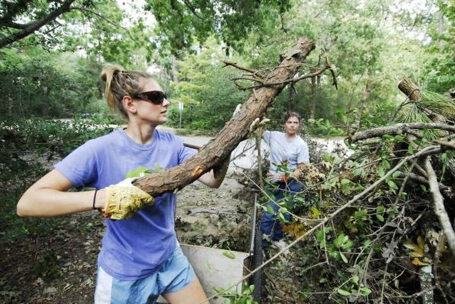 Administrative Manager Keely Pate and Lori Hutson help clear fallen branches caused by Hurricane Ike at the Houston Arboretum & Nature Center on Sept. 23, 2008. Photo: Tony Bullard