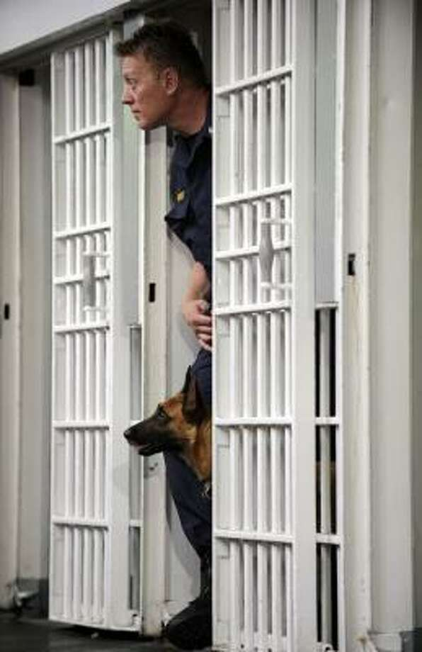 Sgt. David Brosky, a Maryland corrections officer, demonstrates how his dog Alba, a Belgian malinois, finds cell phones smuggled in to inmates. How a dog is trained to find the contraband is a top secret. Photo: MARVIN JOSEPH, WASHINGTON POST