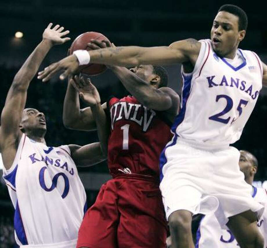 Kansas forward Darrell Arthur (right) and guard Brandon Rush put the defensive clamps on UNLV guard Wink Adams in the first half. Photo: Dave Weaver, AP