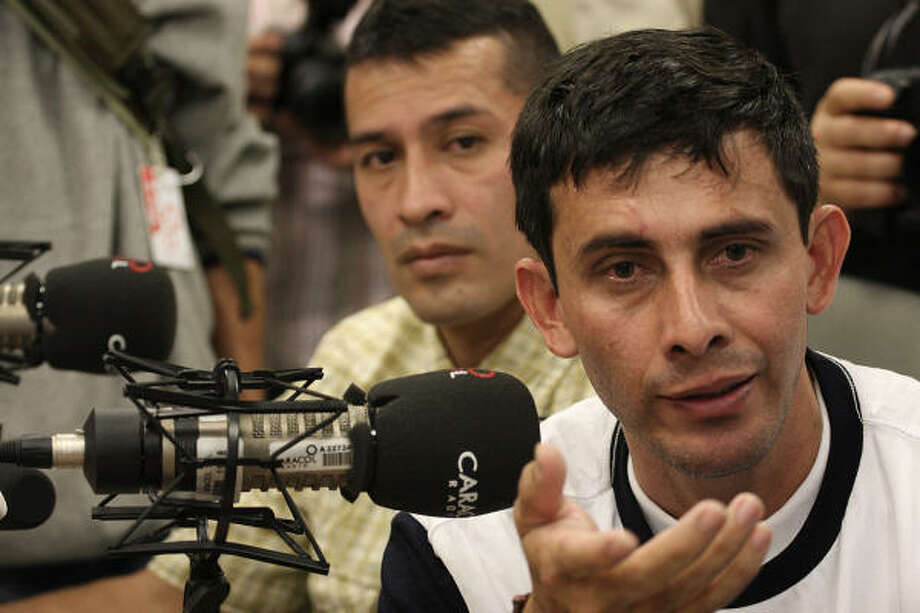 Two former hostages, police Officer Armando Castellano, right, and Officer Julio Buitrago send messages to the remaining rebel-held captives during an appearance on the Voices of Kidnapping program on Bogota's Caracol Radio on Sunday. Photo: William Fernando Martinez, Associated Press