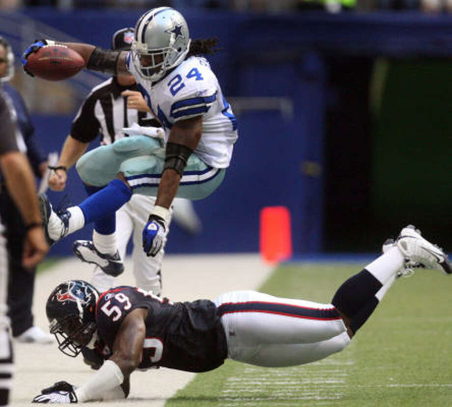 Cowboys running back Marion Barber leaps over Texans defender DeMeco Ryans, who is the leader of the team's struggling defense. Photo: LOUIS DeLUCA, MCT