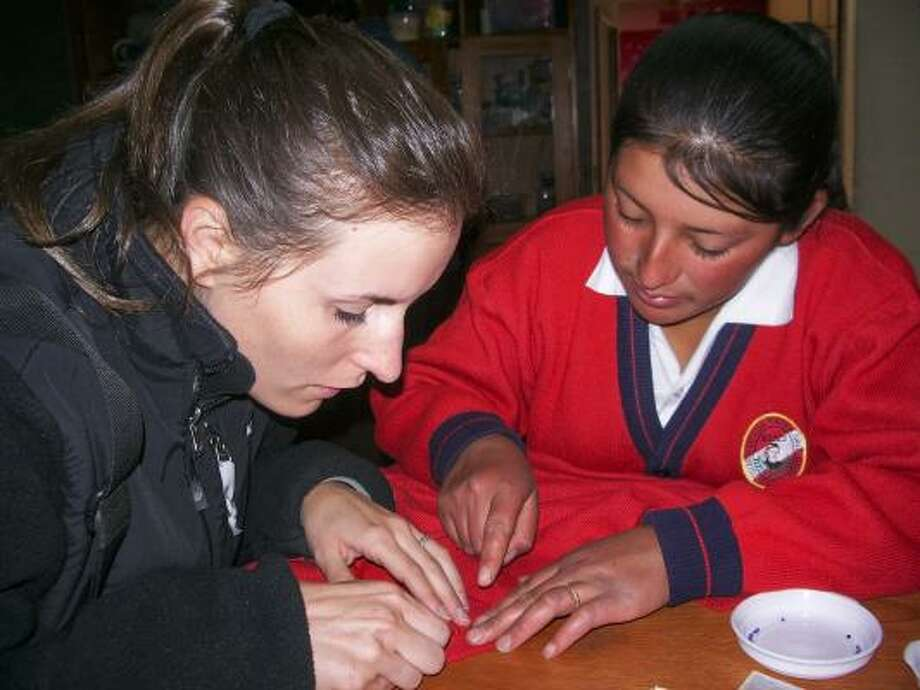 Cristina Boyer, left, helps with a sewing project at the People of the House of the Sun shelter for children in Cusco, Peru. Photo: Courtesy, JENNIFER KIRSTEIN