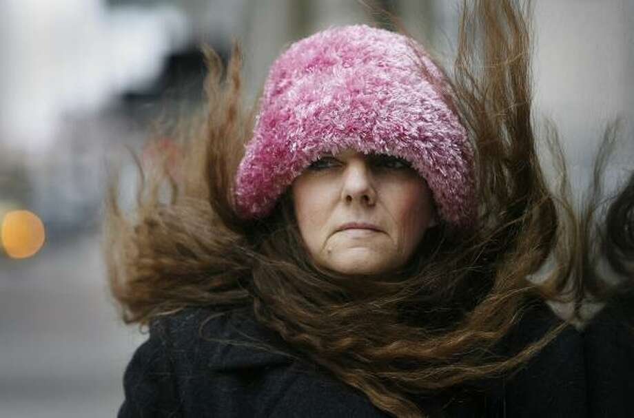 Darlene Tucker waits for a bus as cold weather hit Houston on Monday. She was downtown for an appointment and had been enduring the chill for 30 minutes. Photo: ERIC KAYNE, CHRONICLE