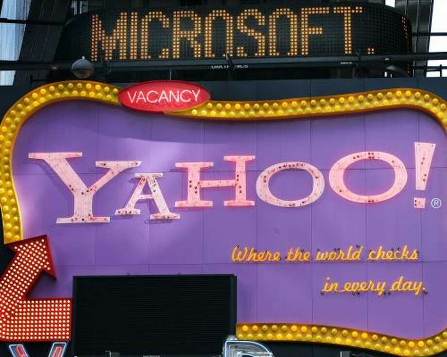 ** FILE ** A Times Square news ticker flashes a headline about Microsoft above a billboard for Yahoo! in New York in this Friday, May 4, 2007 file photo. Microsoft Corp. has pounced on slumping Internet icon Yahoo Inc. on Friday, Feb. 1, 2008, with an unsolicited takeover offer of $44.6 billion in its boldest bid yet to challenge Google Inc.'s dominance of the lucrative online search and advertising markets. (AP Photo/Mark Lennihan, file) Photo: Mark Lennihan, AP