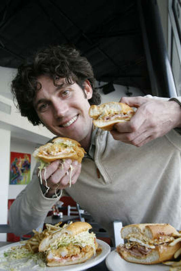 "BB's Cajun cafe owner Brooks Bassler poses with the ""Bedtime in the Bayou"" shrimp po' boy, left,  and the ""Morning Majic"" fried egg and ham po' boy. Photo: James Nielsen, Houston Chronicle"