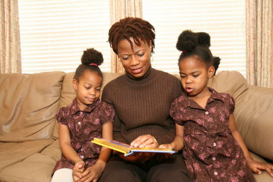 Angela Crawford reads a book to her twins, Faith, 3, on the left, and Grace.  Angela is president of Mocha Moms South Houston Chapter. Photo: Suzanne Rehak, For The Chronicle