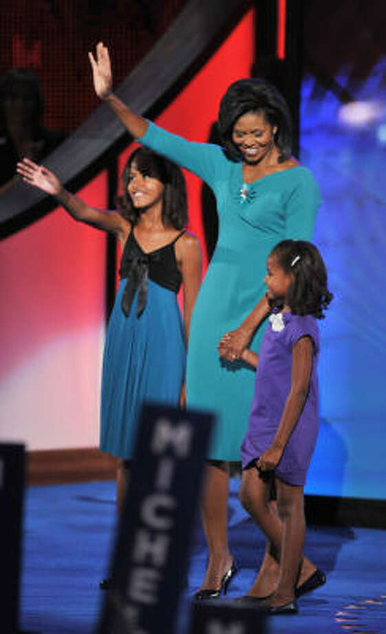 Michelle Obama, wife of US Democratic presidential candidate Barack Obama, brings daughters Malia, left, and Sasha on stage after her speech. Photo: PAUL J. RICHARDS, AFP/Getty Images