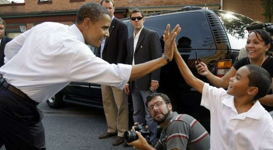 Barack Obama exchanges high-fives Thursday with a boy outside the Columbia Market House in Columbia, Pa. Photo: ALEX BRANDON, ASSOCIATED PRESS