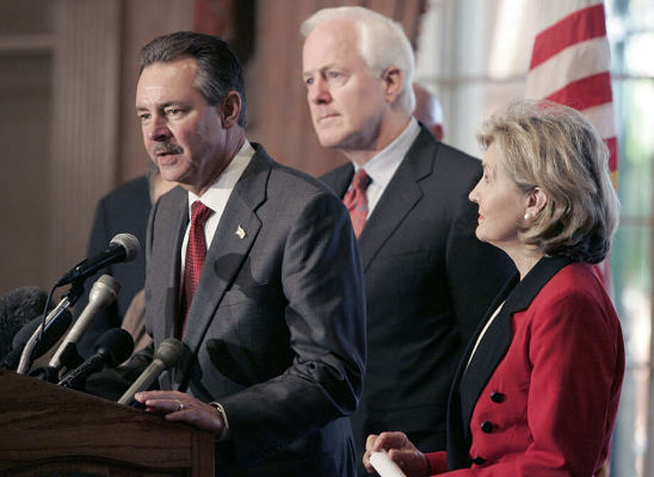 Backed by U.S. Sens. John Cornyn, R-Texas, center, and Kay Bailey Hutchison, R-Texas, Federal Emergency Management Agency Administrator David Paulison speaks at a press conference after meeting with local officials about the problems of finding housing for Texans displaced by Hurricane Ike. Photo: Pat Sullivan