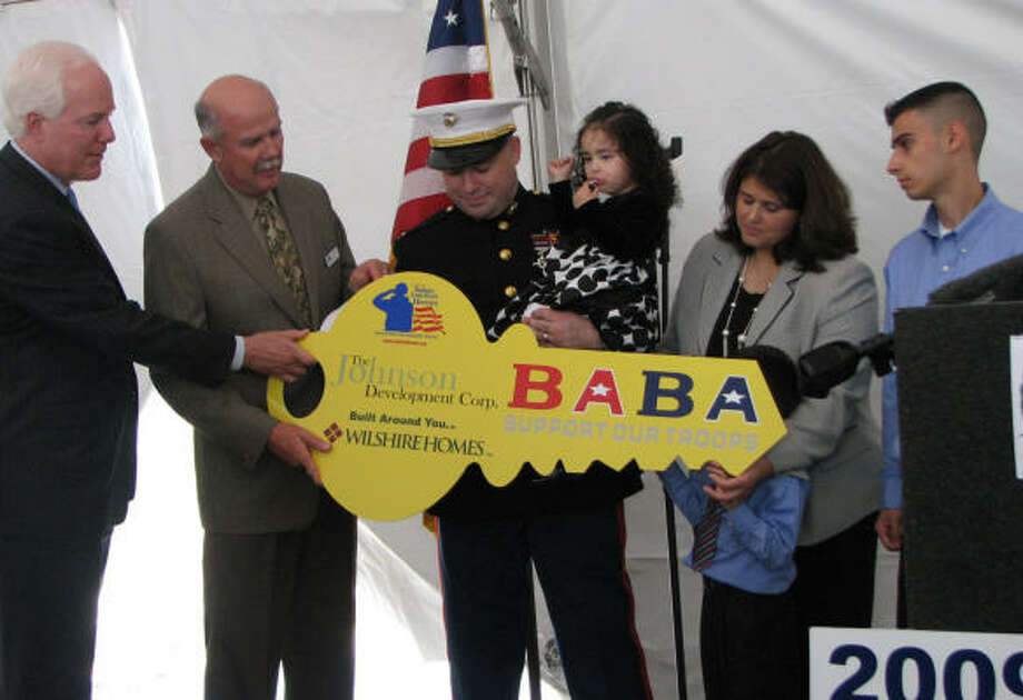 Marine Lt. Erasmo Valles, left, his daughter Tatiana and wife Sandra receive an honorary key to their home.