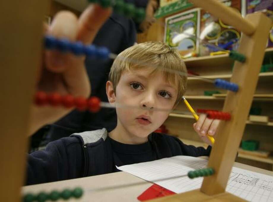 Garrett Leath, 7, works on a math lesson during a class for first- through third-graders at Woodrow Wilson Elementary. Photo: JAMES NIELSEN, CHRONICLE