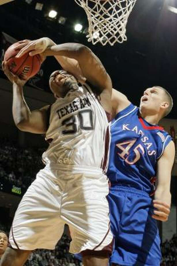 Texas A&M's Joseph Jones, left, gets tangled up with Kansas' Cole Aldrich in the first half Saturday. Photo: DAVID J. PHILLIP, AP