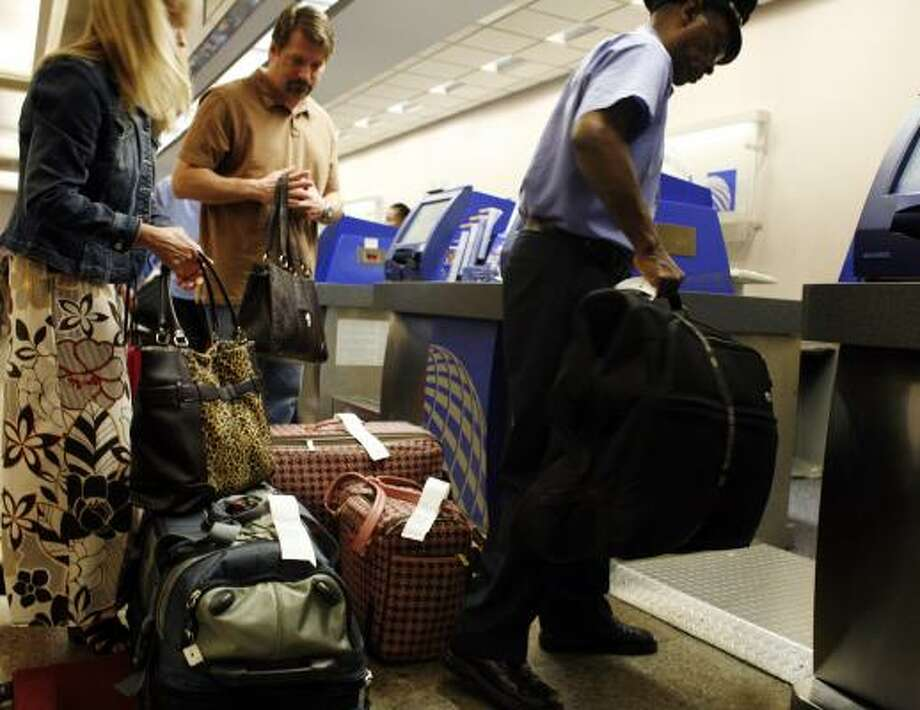 Skycap Robert Bernard helps Brenda and Eric Cooper check in their luggage at the Continental counter at Bush Intercontinental Airport on Friday. Airlines are hoping to cut down on luggage, which will help to conserve fuel. Photo: ERIC KAYNE, CHRONICLE