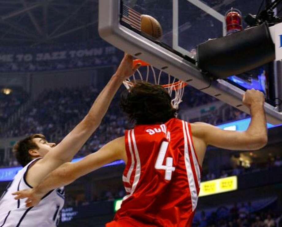 Utah center Mehmet Okur, left, rejects a shot attempt by the Rockets' Luis Scola in the first quarter Saturday night. Photo: NICK DE LA TORRE, CHRONICLE