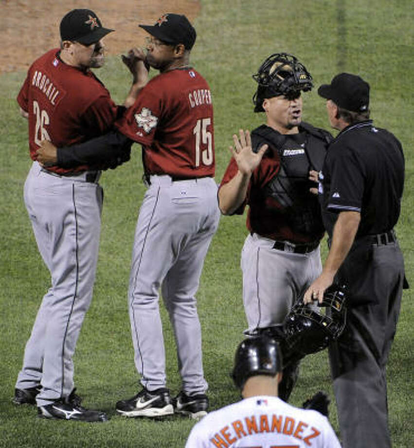 Astros pitcher Doug Brocail is held back by manager Cecil Cooper, as catcher Humberto Quintero talks to home plate umpire Ed Hickox about a disputed call during the seventh inning against the Baltimore Orioles on Tuesday. The Orioles defeated the Astros, 6-5, at Oriole Park at Camden Yards in Baltimore. Photo: Gene Sweeney Jr, MCT
