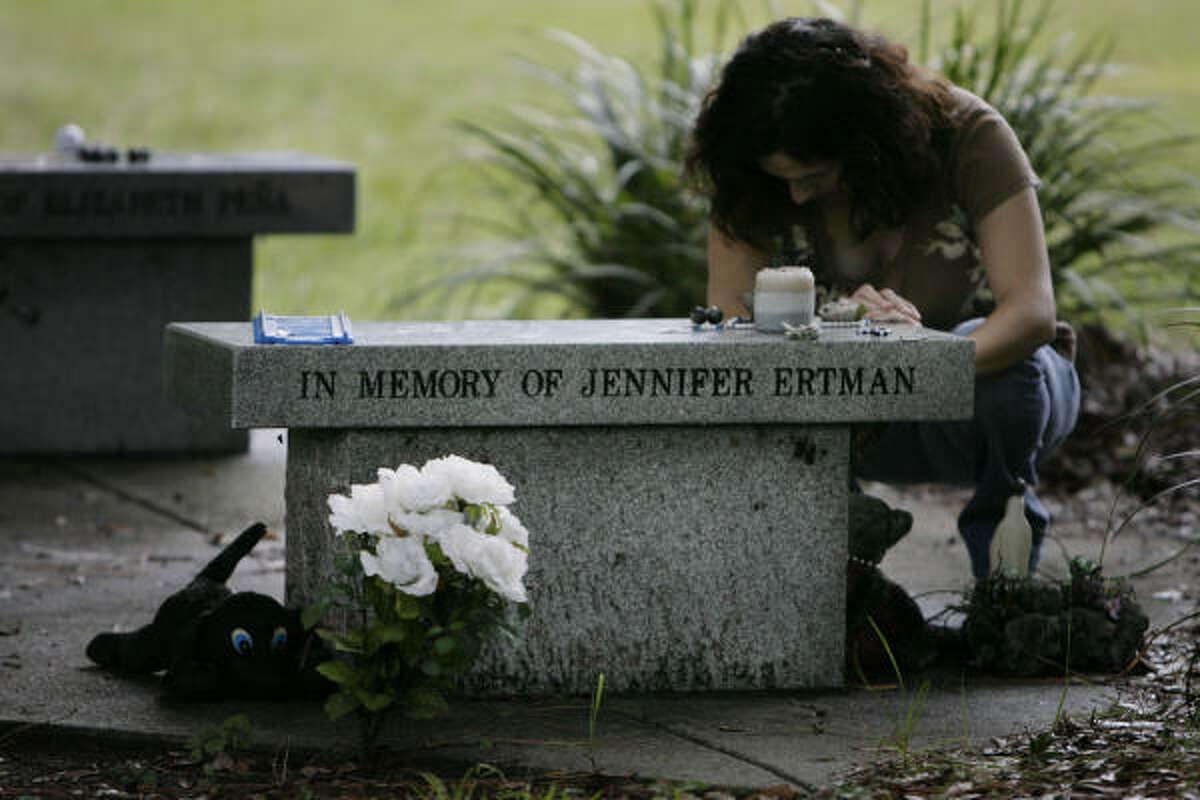 Sylvia Orta Perez, 32, who had gym class with Jennifer Ertman in middle school, takes a moment at the memorial site for Ertman and Elizabeth Peña in TC Jester Park on Tuesday. Asked what memories she had of Ertman, Perez said,