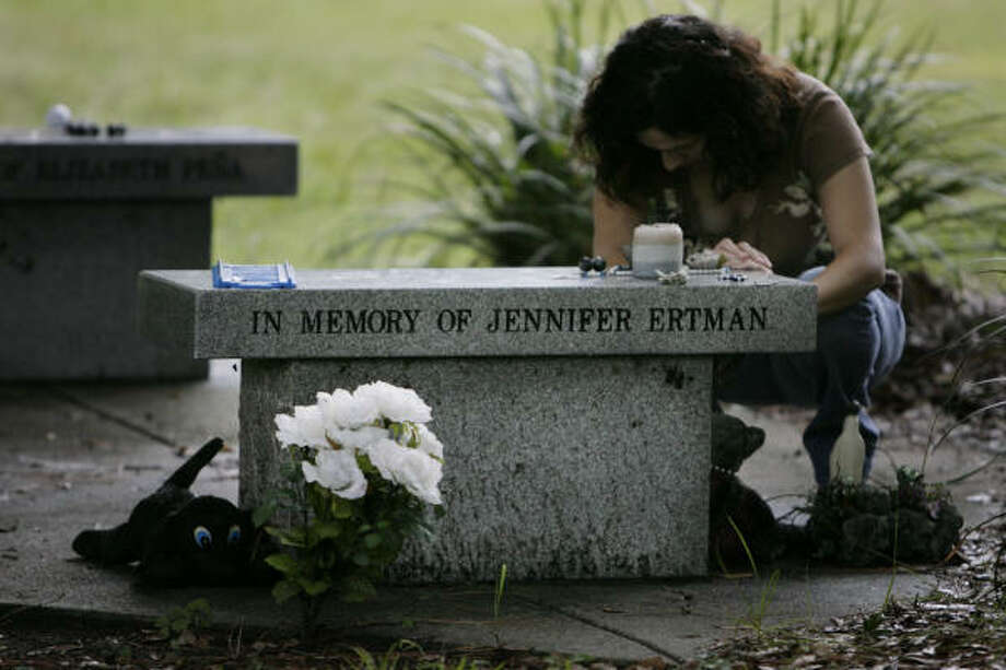 "Sylvia Orta Perez, 32, who had gym class with Jennifer Ertman in middle school, takes a moment at the memorial site for Ertman and Elizabeth Peña in TC Jester Park  on Tuesday. Asked what memories she had of Ertman, Perez said, ""She had a beautiful smile."" Photo: Eric Kayne, Chronicle"