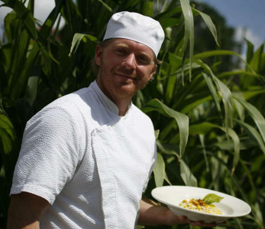 The corn is as high as an elephant's eye behind Patrenella's, and executive chef Ryan Hildebrand makes good use of it. He's holding his Risotto With Candied Corn. Photo: Sharon Steinmann, Chronicle