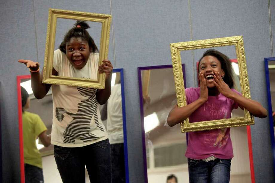 metro - Betty Ngaima, 12, left, who was born in Sierra Leone but later moved to Liberia, and Chidera Ugwokaegbg, right, who was born in the U.S. but her parents are from Nigeria, react as various emotions are called out including an emotion for winning the lottery for the children to show inside the frames during the ESL (English as a Second Language) Summer Class for refugee children at Saint Francis Episcopal Church in San Antonio on Saturday, July 9, 2011. LISA KRANTZ/lkrantz@express-news.net Photo: LISA KRANTZ, LISA KRANTZ/lkrantz@express-news.net / SAN ANTONIO EXPRESS-NEWS