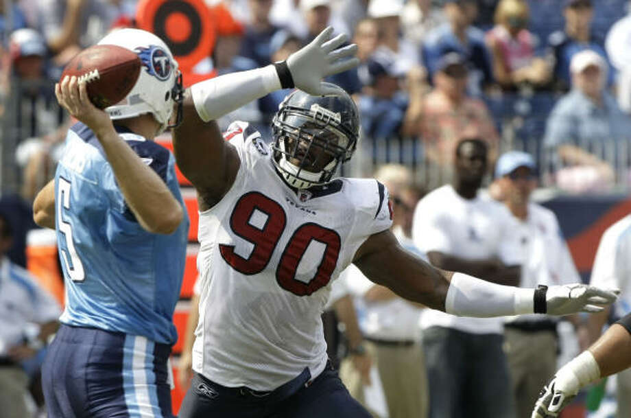 Titans quarterback Kerry Collins throws a pass over the outstretched arms of Texans defensive end Mario Williams in the second quarter. Photo: Brett Coomer, Chronicle