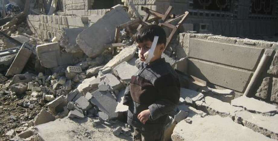 Omar Abdullah, 12, stands in front of his destroyed home Friday in Fallujah. Two police stations were destroyed by suicide truck bombers Thursday, killing 17 people and wounding more than 100. Photo: BILAL FAWZI, ASSOCIATED PRESS
