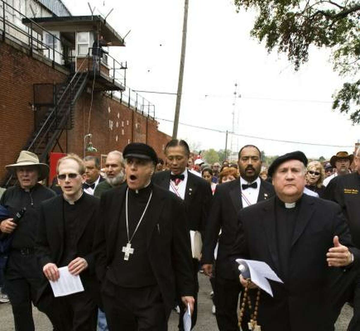 Cardinal Daniel DiNardo, center, leads marchers from Huntsville's Planned Parenthood to the Walls Unit on Monday.