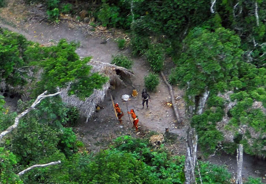 This photo released Thursday by the Brazilian Indian Protection Foundation (FUNAI) shows two members of a recently discovered indigenous tribe, with their bodies painted in bright red, aiming their bows and arrows at the aircraft from which the pictures were taken while another looks on. Photo: GEISON MIRANDA, AFP/Getty Images