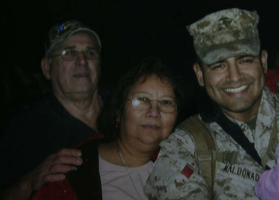 A family photo shows Gloria McInnis, 55, with her  husband, Raymond McInnis, left, and her son, Jose Angel Maldonado, who is on his second tour in Iraq. Gloria McInnis was killed in an explosion Wednesday at the Goodyear plant in southeast Houston, where she had worked for 31 years. Photo: Julio Cortez, Chronicle