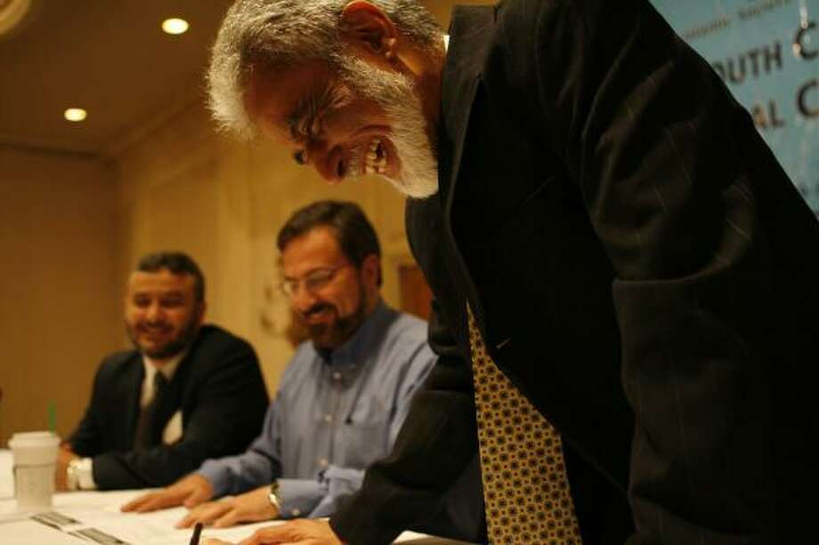 From right, Sayyid Syeed, Louay Safi and Safaa Zarzour laugh at the speakers table Saturday in Houston during the regional conference on Islam in the U.S. Photo: JAMES NIELSEN, CHRONICLE