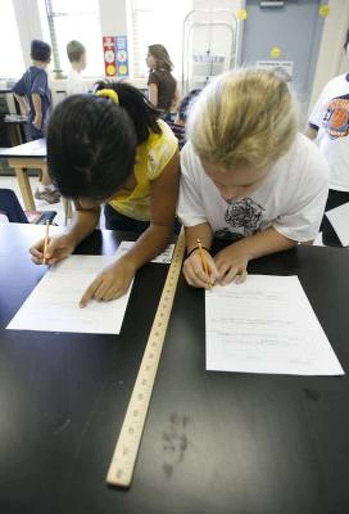 Fifth-graders Annum Sadana, left, and Julianna Pierce write down what they observed in science class at Roberts Elementary.