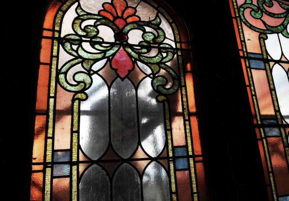 A workman can be seen through the restored stained glass windows of Vineyard Community Church in Cohoes Friday Aug. 5, 2011.   (John Carl D'Annibale / Times Union) Photo: John Carl D'Annibale / 00014129A