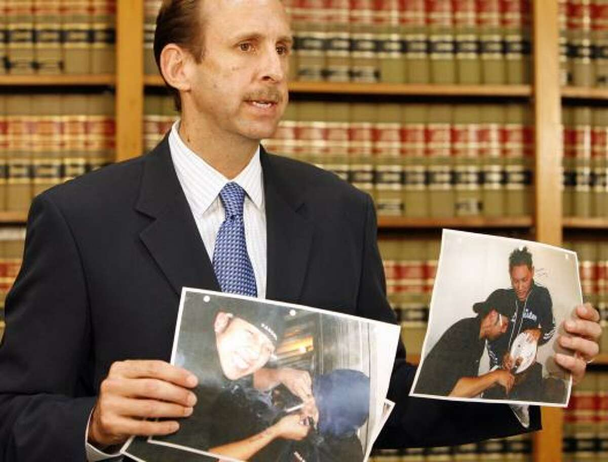 Randall Sorrels, an attorney representing the family of Jack Phoummarath, shows photos at a news conference July 15 of fraternity members forcing Jack to smoke through his nose.