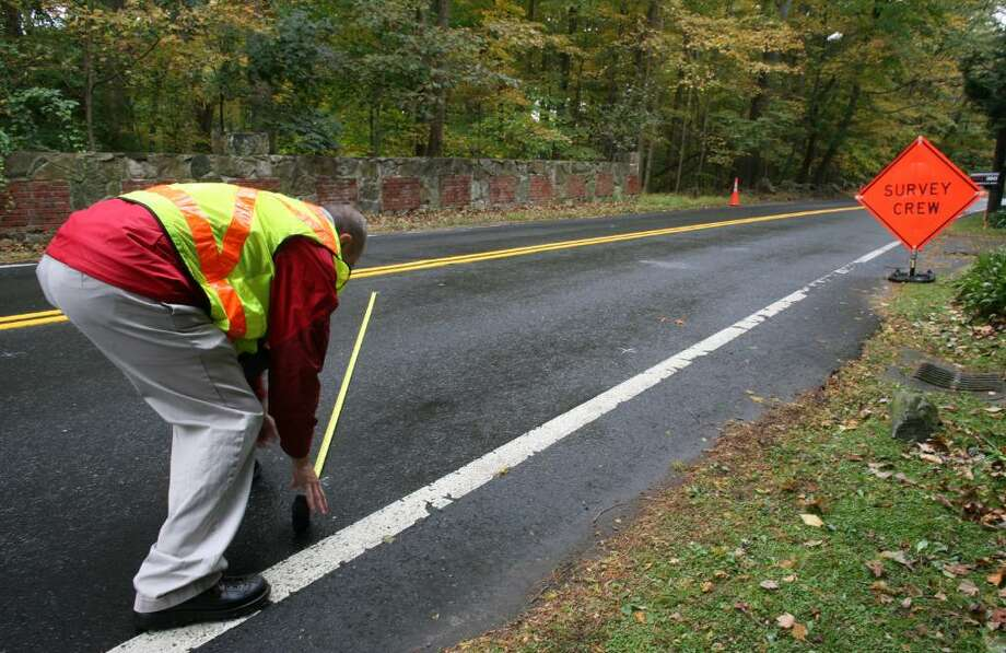 An accident investigator takes measurements on Riversville Road Friday morning after Thursday afternoons fatal accident involving a motorcyclist. Photo: David Ames / Greenwich Time