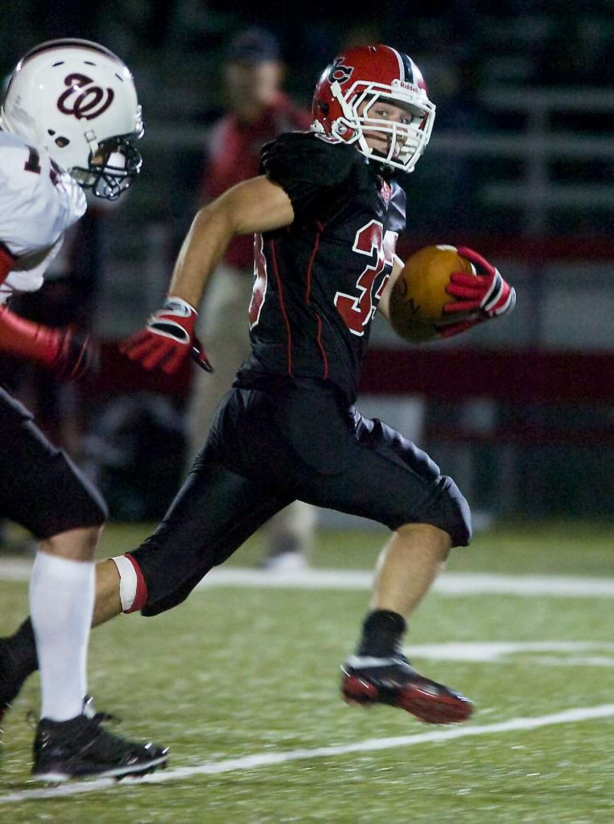New Canaan High School's Cody Newton carries the ball against Fairfield Warde in football action at New Canaan.