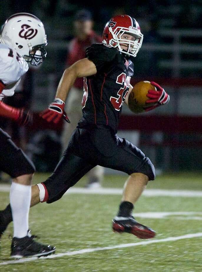 New Canaan High School's Cody Newton carries the ball against Fairfield Warde in football action at New Canaan. Photo: Kathleen O'Rourke / Greenwich Time